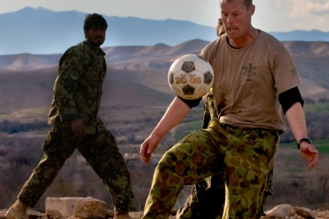 Royal Australian Air Force Cpl. Chris Dickson, combat cameraman for Combined Team Uruzgan, juggles a soccer ball with his legs Feb. 25 in Mirabad Valley, Afghanistan, while Afghan National Army soldiers attempt to guard him. (U.S. Army photo by Spc. Edward A. Garibay, 16th Mobile Public Affairs Detachment)