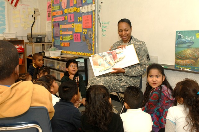 """Maj. Denise Newson, training officer, First Army G-3, reads """"Stone Soup"""" to LaToya Adams' second grade class at W.A. Fountain Elementary School March 2. Newson and other First ArmySoldiers went to the school, one of its education partnership schools, as part of Read Across America Day, which celebrates the birthday of Theodor Seuss Geisel, better known as Dr. Seuss."""