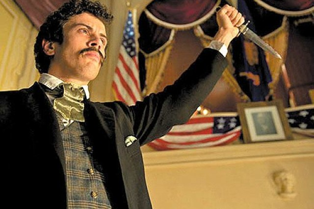 John Wilkes Booth (Toby Kebbell) raises a dagger in triumph after assassinating President Abraham Lincoln.