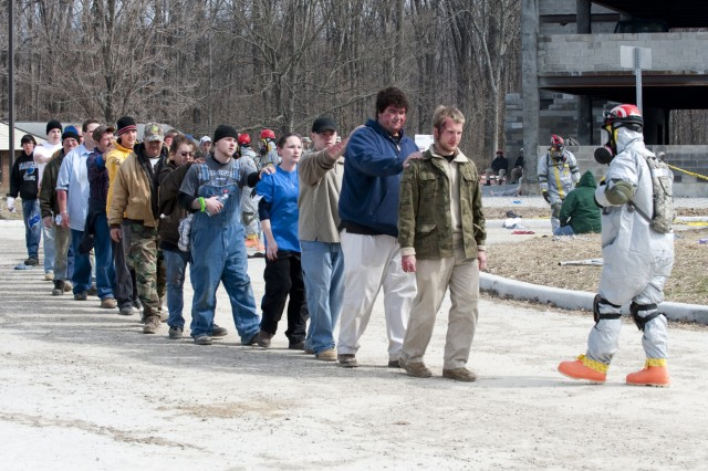 Role-players lined up after being found by members of the Colorado National Guard's Chemical, Biological, Radiological and Nuclear Enhanced Response Force Package Decontamination Team following a mock nuclear blast during Vibrant Response 11.1, a U.S. Northern Command homeland emergency response exercise being conducted through March 20, at the Muscatatuck Urban Training Complex in Butlerville, Ind., which tests the capabilities of the nation's emergency response network.