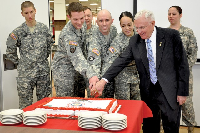 Dr. Robert Schloesser, director of Family, Morale, Welfare and Recreation for U.S. Army Garrison Wiesbaden, joins fellow Wiesbaden Soldiers in cutting a cake to kick off this year's Army Emergency Relief fundraising campaign. the annual campaign continues through May 15.