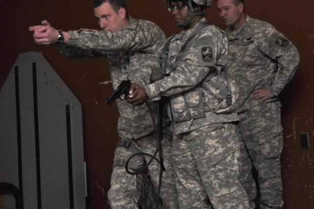 Staff Sgt. Andrew Knight, a operation non-commissioned officer for the 100th Missile Defense Brigade (Ground-based Midcourse Defense), shows Sgt. 1st Class  Mary Thompson how to aim  her M-9 pistol during the units trip to the EST 2000 at Fort Carson, Feb 24, 2011. The unit later went to the live range on Fort Carson to qualify March 10.