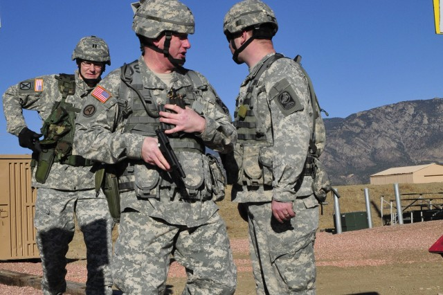 Staff Sgt. Bryan Ginetti, planning and operations non-commissioned officer, and Capt. Robert Waddington, assistant planning and operations officer for the 100th Missile Defense Brigade (Ground-based Midcourse Defense), walk onto the live shooting range during the units pistol qualification range at Fort Carson, March 10, 2011.