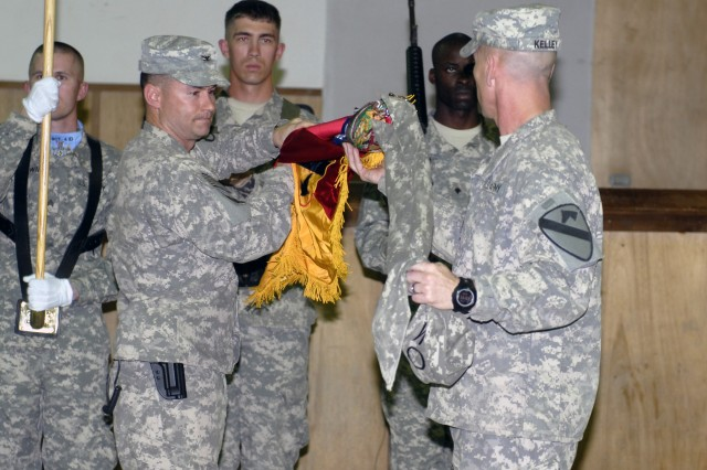 CONTINGENCY OPERATING BASE ADDER, Iraq - Col. Douglas Crissman and Command Sgt. Maj. Ronnie Kelley with 3rd Advise and Assist Brigade, 1st Cavalry Division uncase the brigade's colors at a transfer of authority ceremony March 12. The Greywolf Brigade assumed authority of the Muthanna, Dhi Qar, Maysan and Basrah Provinces of United States Division - South from the 3rd Advise and Assist Bde., 4th Inf. Div. of Fort Carson, Colo.