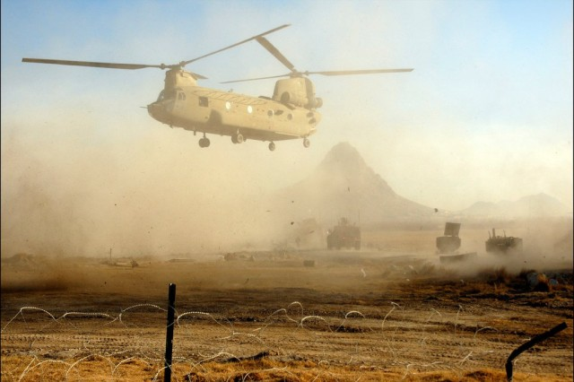 A Chinook helicopter passes over an International Security Assistance Forces convoy in order to drop Soldiers off outside Combat Outpost Johnston in the Arghandab District.