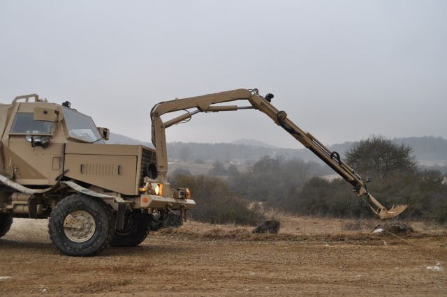 Soldiers from 42nd Clearance Company, 54th Engineer Battalion operate a Buffalo mine protected vehicle in order to interrogate a suspected improvised explosive device placed along the road in Hohenfels Training Area, Feb. 27.