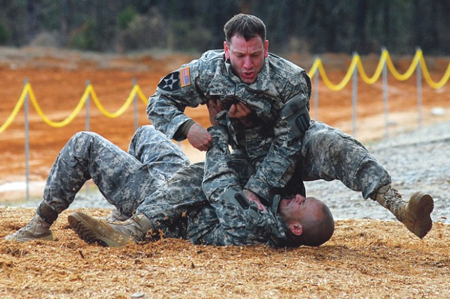 Instructors from the Army Combatives School grapple Thursday during a hands-on training exercise in front of hundreds at Red Cloud Range. The demonstration was one of several over the course of the day to show visitors the types of military training conducted at Fort Benning.
