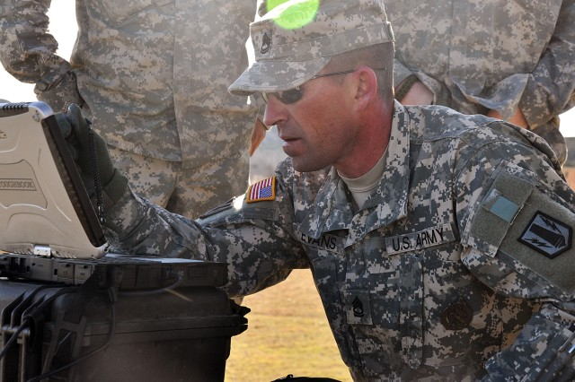 Sgt. 1st Class Randell Evans, master Raven trainer with 2nd Battalion, 20th Field Artillery Regiment, 41st Fires Brigade, loads programs onto a laptop that is synchronized with the Raven RQ-11B unmanned aerial vehicle during the 41st Fires Bde. and the 2nd Battalion Combat Team re-certification training at the House Creek Assault Course, Fort Hood, Texas, March 10-11.