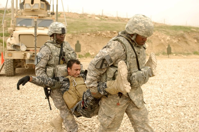 CONTINGENCY OPERATING SITE MAREZ, Iraq - Pfc. Luther Alston (right) and Spc. Oriola Owokoya (left), both medics assigned to Headquarters and Headquarters Battery, 5th Battalion, 82nd Field Artillery Regiment, 4th Advise and Assist Brigade, 1st Cavalry Division, demonstrate a field-expedient method for carrying a casualty during training at the Ghuzlani Eagle Training Center, March 9, 2011. Alston, a native of Warrenton, N.C., and Owokoya, a native of Lagos, Nigeria, taught Iraqi policemen of 3rd Federal Police basic medical skills as part of a six-day training class to develop the Iraqi Police unit's tactical capabilities.