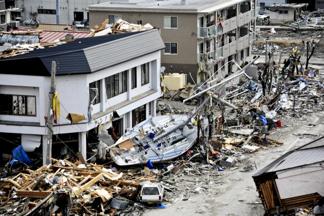 A fishing boat crashes against a building after being swept ashore during a massive tsunami that hit the Japanese fishing port of Ofunato, Japan, March 15, 2011. The town was devastated by an 8.9-magnitude earthquake that triggered the destructive tsunami. U.S. servicemembers have been assisting in relief efforts in the country.