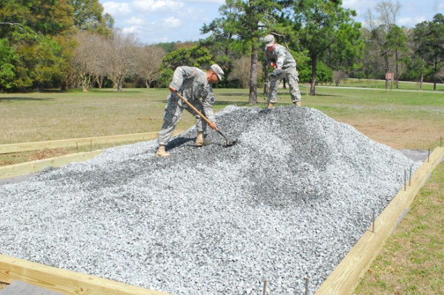 Spc. Rene Filpo and Spc. Zachary Followwill shovel gravel Monday to fill a wooden frame for one of two tank display pads. A team of eight Soldiers from the 11th Engineer Battalion's 63rd Engineer Company worked on the project, which is expected to be complete next week.