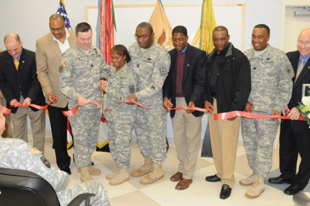 Current and former leaders of the 262nd Quartermaster Battalion, 23rd QM Brigade, join Col. (P) Gwen Bingham, Quartermaster School Commandant, as she cuts the ribbon that marked the official opening of the 262nd QM Battalion headquarters building along A Avenue Friday. Also pictured from left are retired colonels Steve Green, William Jenks and Al Davis; Battalion Commander Lt. Col. Hugh Davis; Command Sgt. Maj. Douglas Washington, 262nd QM Battalion CSM; retired Lt. Col. Keith Orage; retired Command Sgt. Maj. Tony Moore; Lt. Col. Ronald Childress; and retired Command Sgt. Maj. Stephen Ball.