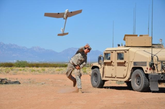 Cpl. Kennith Parish launches the Raven Unmanned Aircraft System for a test reconnaissance flight.