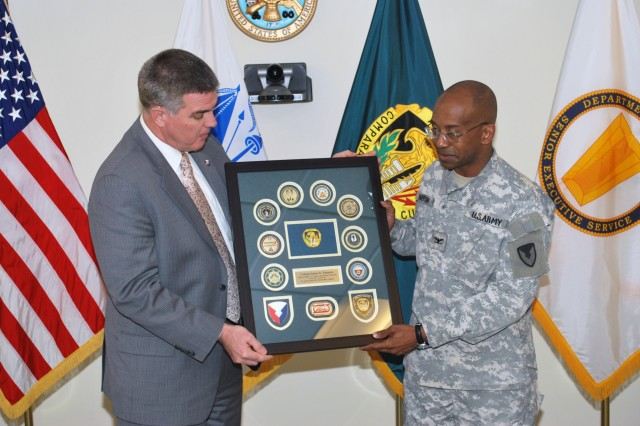 Col. James E. Simpson, Army Contracting Command chief of staff, receives a command senior leader coin display from Jeff Parsons, ACC executive director, at his farewell ceremony March 14, at ACC Headquarters, Fort Belvoir, Va.  Col. Simpson, chief of staff since July 2010, will soon depart for Baghdad where he will serve as the senior Army contracting official supporting Operation New Dawn.  Sally George, deputy chief of staff, will succeed him on an interim basis.  Col. Jeffrey Gabbert, Defense Contracting Management Agency, central region commander in Huntsville, Ala., will become the ACC chief of staff in June.