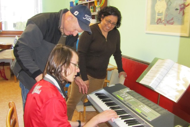 Sgt. 1st Class Brett McHaney, Warrior Transition Unit-Vilseck platoon sergeant, and his wife, Rachel, show one of the teenagers how to use a keyboard during a visit to the DD Plana Orphanage in Plana, Czech Republic, March 4. Volunteers from the WTU donated toys, clothes, school supplies and shoes to the orphanage.