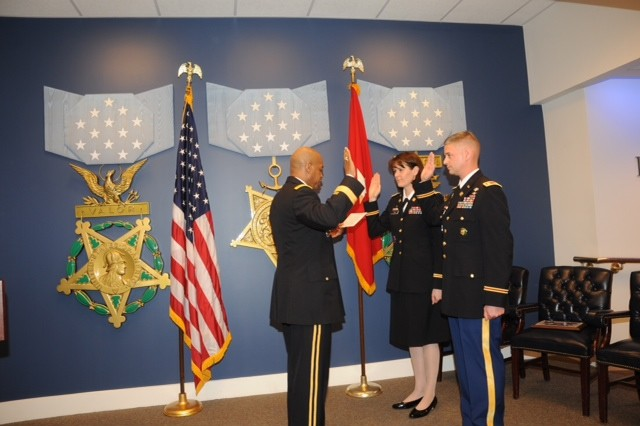 Brig. Gen. Larry D. Wyche (left) leads new lieutenant colonels Robert and Renee Mann through the oath of office pledge after pinning on their new rank.