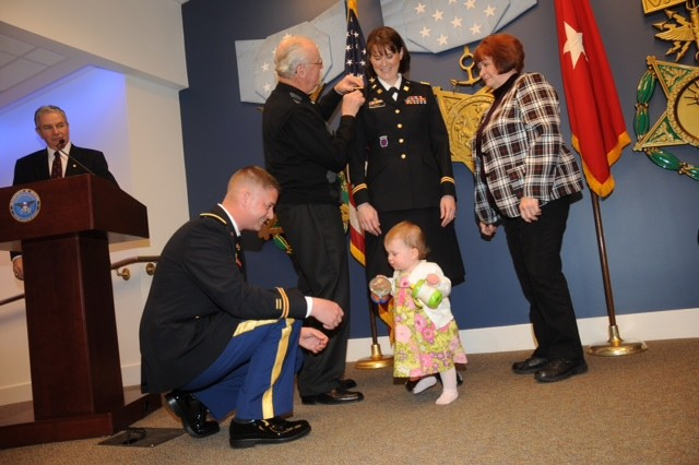 Lt. Col. Renee Mann is all smiles as her parents, Joseph Paulus and Shirley Miller, assist in placing on her new rank while newly promoted husband Lt. Col. Robert Mann shares a moment with their daughter Olivia.  The Manns were promoted in a joint ceremony in the Pentagon Hall of Heroes March 11.