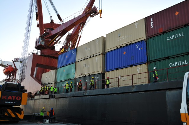 Workers start boarding the MV Virginian at the Kuwait Naval Base to begin the unloading process of over 400 containers on March 19, 2011.