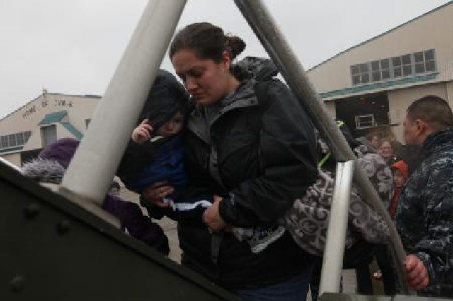 Military family members board a plane March 21 in Hoshu, Japan. A voluntary departure of family members from the island was authorized by the Secretary of Defense and Secretary of State and Department of the Army set up a web site to assist civilians there.