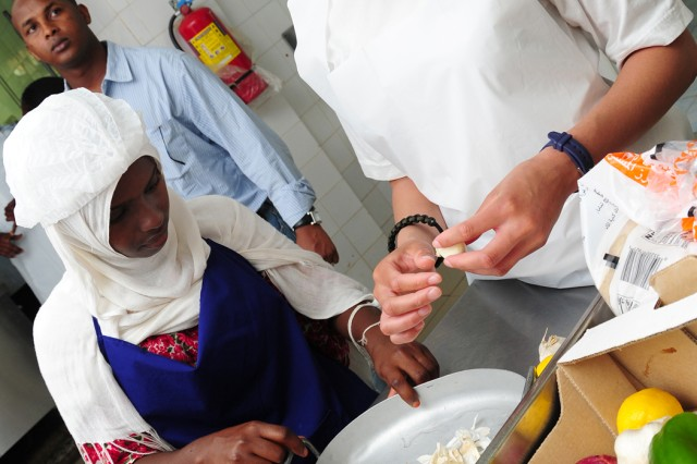 U.S. Navy Petty Officer 2nd Class Sasha Hutchinson (right), and Deke Ahmed, Arta Culnary School student, break garlic for a meal prepared by the Community Action Volunteer group March 12, 2011, in Arta, Djibouti.