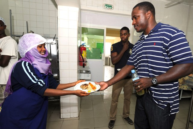 Arta Culinary School student Eissa Ahmed Gnnan hands out a dish of chicken and rice March 12, 2011.