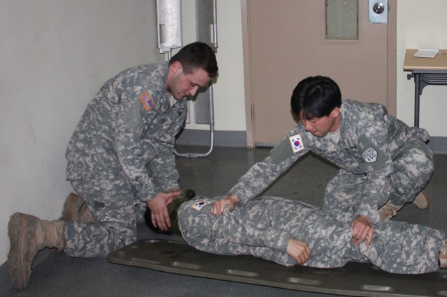 Pfc. Ibrahim Ahmed (left) demonstrates how to properly secure and transport a casualty suffering  from head and neck injuries, utilizing a litter, during the Combat Life Saver Course March 11.