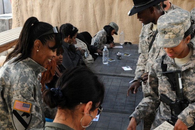 """BABIL, Iraq - Soldiers file along a table to get autographs from the ladies of an all female comedy troupe on Contingency Operating Site Kalsu Monday. The ladies performed their show, """"Its Not That Time of the Month"""", in support of deployed servicemembers as well as Women's History Month. US Army photo by Staff Sgt. Garrett Ralston (110314-A-8856R-208)"""