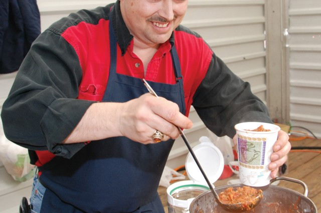 """Brad Moore spoons a ladleful of his prize-winning red chili into a cup for judges to sample during the U.S. Army Garrison Stuttgart Chili Cook-off March 13. Moore, who worked as a cook in the Marine Corps for eight years, made his red chili with ground buffalo meat and Italian sausage. He also made a seafood chili and a """"people's choice"""" chili - all in under three hours. The cook-off was sponsored by the Family and Morale, Welfare and Recreation Community Recreation Division.  Next year's event will be an International Chili Society-sanctioned event."""