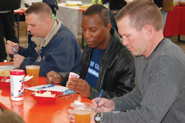 Chili cook-off judges Col Carl. D. Bird, garrison commander (from left), Command Sgt. Maj. Anthony M. Bryant, garrison command sergeant major, and Lt. Col. Rich Weaver, U.S. Africa Command commandant, deliberate over the many chili entries at the USAG Stuttgart Chili Cook-off March 13. To select the winners, judges used International Chili Society guidelines based on flavor, meat texture, consistency, blend of spices, aroma and color.