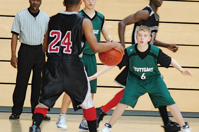 """Jeffrey Kaczmarek (center) and Bryce Hill defend against Mannheim in the semifinal Western Regional game on March 13. """""""