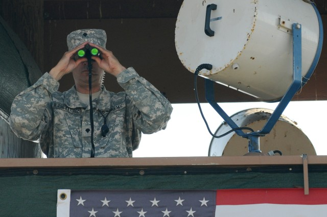 A soldier with Company B, 1-296th Infantry attached to the 525th Military Police Battalion keeps a watchful eye on the confines of Joint Task Force Guantanamo's Camp Delta.