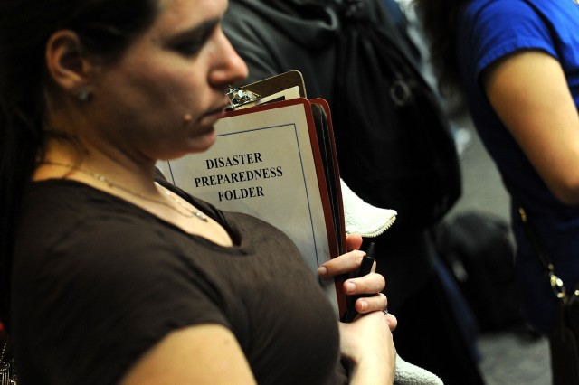 A woman clutches a disaster preparedness folder while waiting at the Seattle-Tacoma International Airport USO March 19, 2011.