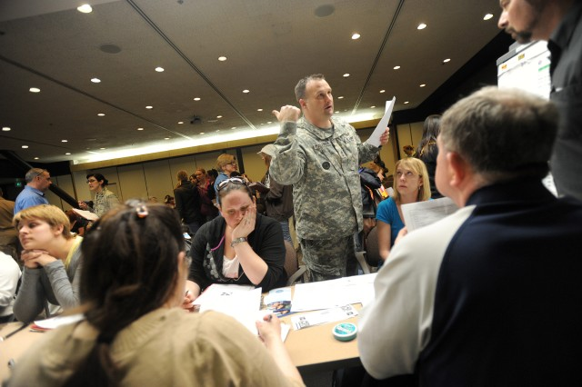 Sgt. 1st Class Christopher Palaniuk talks with officials while assisting military family members arriving from Japan at Seattle-Tacoma International Airport, March 19, 2011.