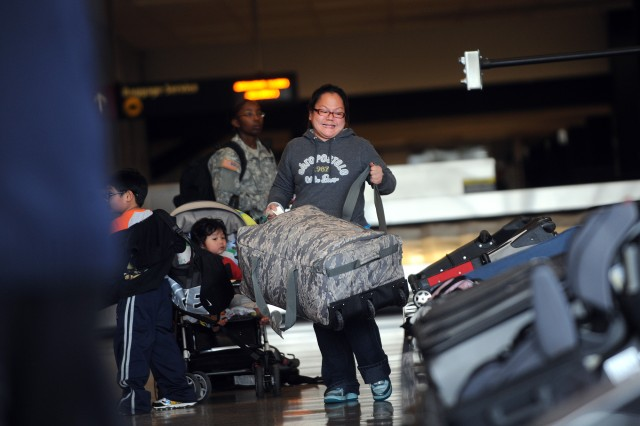 A woman retrieves a bag from a carousel at the Seattle-Tacoma International Airport, March 19, 2011.