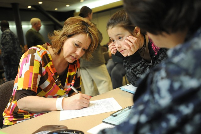 Lt. Cmdr. Jennifer Eichenmuller,  U.S. Navy Judge Advocate, right, helps Desire Mings, left, and her daughter Amanda, 11, fill out paperwork March 19, 2011, at Seattle-Tacoma International Airport.