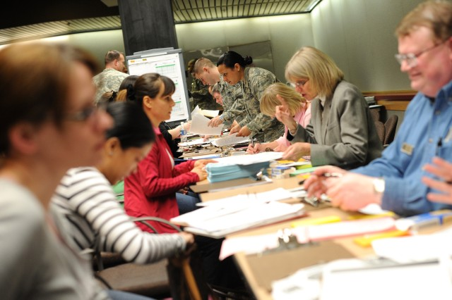 Military personnel help evacuees from Japan fill out paperwork at Seattle-Tacoma International Airport, March 19, 2011.