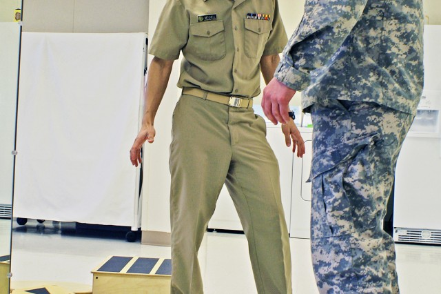 Lt. Cdr. Scott Mitchell, officer-in-charge of the Carl R. Darnall Traumatic Brain Injury clinic at Fort Hood, Texas, helps a patient practice with a balance board at the clinic's Functional Rehabilitation Center.