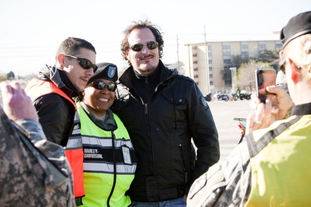 "Staff Sgt. Synetta Peete, 418th Transportation, 13th COSCOM, has her photo taken March 10, at Sadowski Field, Fort Hood,Texas, with Theo Rossi and Kim Coates, actors from the television series, ""Sons of Anarchy."""