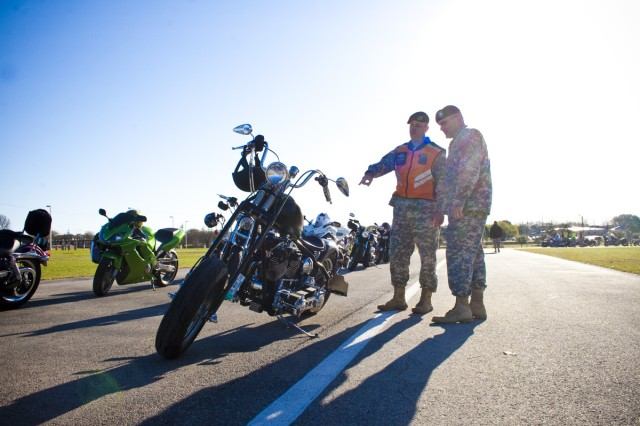 Master Sgt. Richard Sylvia and Lt. Col. Richard Fornili, both with Headquarters and Headquarters Company, 1st Medical Brigade, discuss Fornili's custom motorcycle March 10, at Fort Hood, Texas, before the start of the Motorcycle Mentorship Ride.