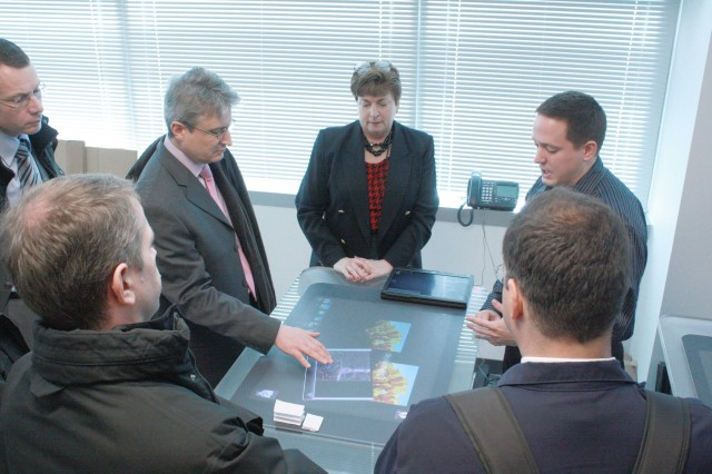 CERDEC engineer Rob Beckinger (right) briefs French delgates on efforts to leverage multitouch technology.