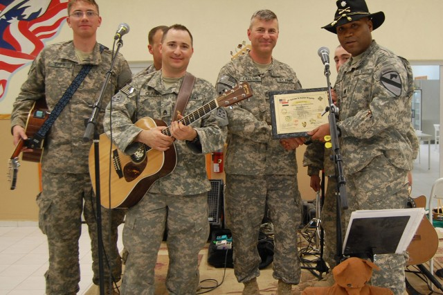 """CONTINGENCY OPERATING SITE MAREZ, Iraq - Lt. Col. Monte Rone, a native of Muskegon Heights, Mich., and executive officer of 4th Advise and Assist Brigade, 1st Cavalry Division, presents a certificate of appreciation to 4th Infantry Division rock band """"H.E.A.T.,"""" for performing for the troops at Contingency Operating Site Marez Memorial Dining Facility, March 14, 2011. The rock band, part of the 4th Infantry Division Ivy Division band, performed a three-hour concert for the deployed Fort Hood Soldiers during dinner at the dining facility."""