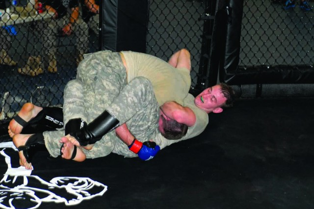 Minnesota's Cody Lincoln, top, battles Adam Therriault of Illinois for the middleweight championship in the cage Sunday at Santiago Fitness Center during the Army National Guard Combatives Tournament.