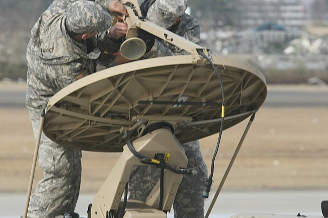 Sgt. Eerrik Byrd and Spc. Eric Martinez, from U.S. Army Japan's Logistics Task Force 35, set up a satellite dish at Sendai Airport, Japan. This communications equipment will help establish a humanitarian assistance and disaster relief supply center to provide supplies to the Japan Ground Self Defense Forces and be distributed to evacuation facilities in the Tohoku area as part of Operation Tomodachi.