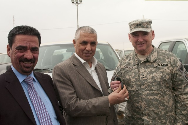 (Right to left) Maj. Gen. Jerry Cannon, deputy commanding general for detention operations and provost marshal general, United States Forces - Iraq, turns over the ceremonial key to staff Maj. Gen. Jawad Kadhem, deputy director, Iraqi Correction Service, and Fuad Ubaid Humood, deputy warden, Taji prison, to complete the turnover of 100 vehicles to the ICS, March 12, in Taji, Iraq.