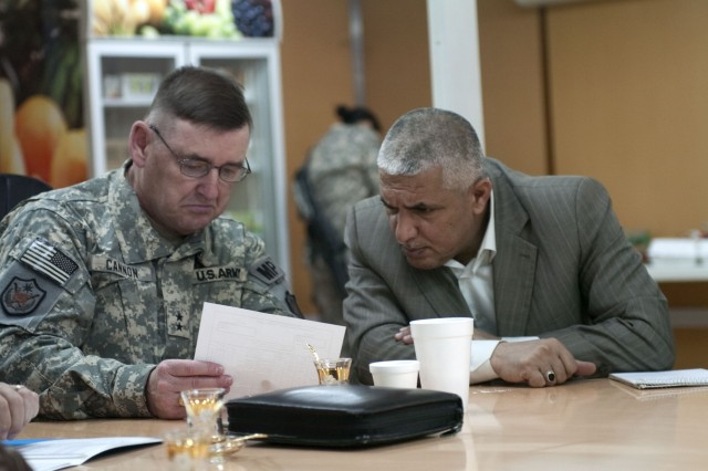 Maj. Gen. Jerry Cannon, deputy commanding general for detention operations and provost marshal general, United States Forces - Iraq, signs paperwork to turnover 100 vehicles to the Iraq Corrections Service as Iraqi staff Maj. Gen. Jawad Kadhem, deputy director, ICS, watches, March 12, in Taji, Iraq.