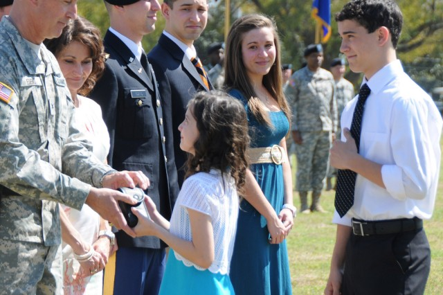 Mia and Liam Edens, children of Brig. Gen. Timothy J. Edens, USAACE and Fort Rucker deputy commanding general, present him with his General Officer Pistol during the Honor Eagle Ceremony March 18 while his wife, Leslie, and children, Brandon, Marshall and Maggie, join them.