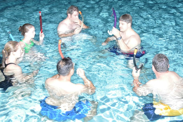 Shawn Holmes, right, Fort Rucker Aquarians dive master, shows the new group of students how to properly use a snorkel during the club's first meeting of the season March 21 at Splash! pool.