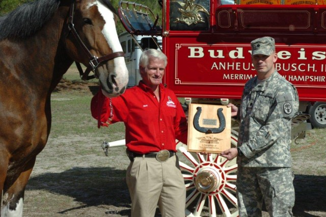 Burton Westbrook, a Clydesdale handler with the Anheuser Busch Corporation, presents a plaque to Lt. Col. William Reitemeyer, commander of the Fort Stewart Warrior Transition Battalion, for his dedication to Soldiers and their Family Members, March 15, at the Bits and Bridle Equestrian Club on Fort Stewart.