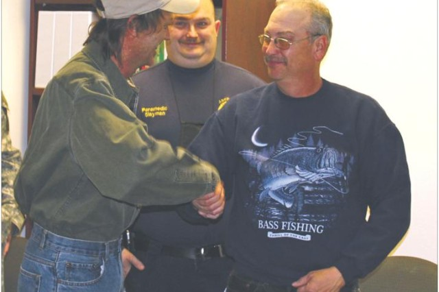 During a March 11 recognition ceremony, Danny Miller (left) shakes the hand of coworker Patrick Meehan, who helped save Miller's life by using CPR.