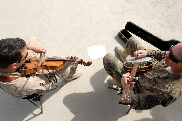 U.S. Army Col. John Sims, chief of information effects for ISAF Regional Command (South), and Canadian Air Force Capt. Paul Dacier, officer in charge of priority air mission requests for RC-South, play bluegrass music together at the RC-South headquarters, Friday, March 18, 2011, at Kandahar Airfield, in Kandahar, Afghanistan.
